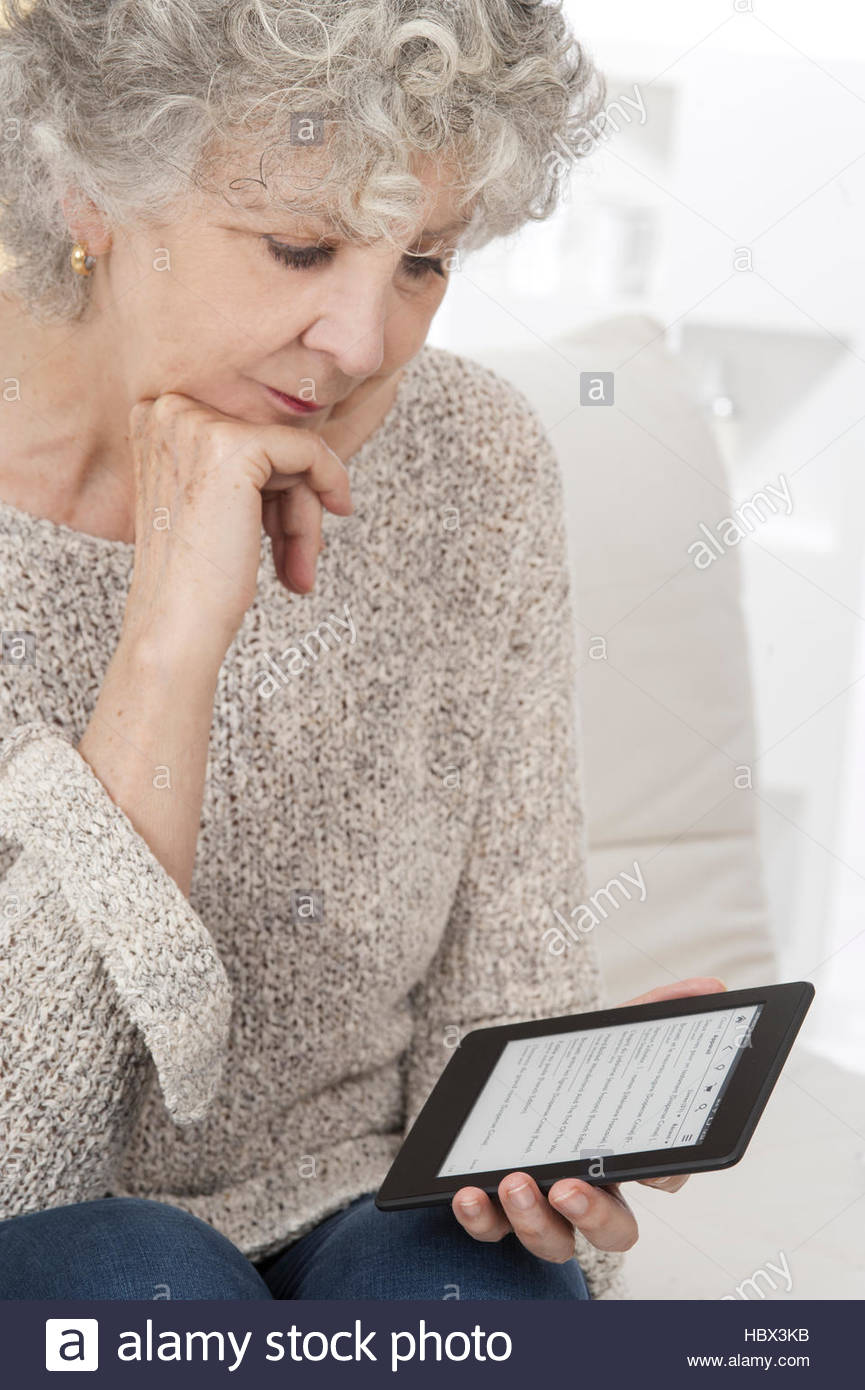 MODEL RELEASED. Woman reading ebook with hand on chin. - Stock Image