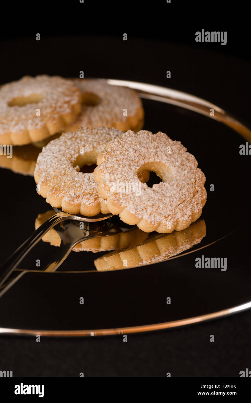 Biscuits reflected on a silver plate - Stock Image