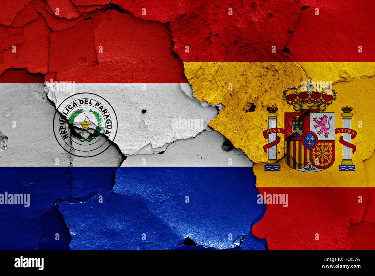 flags of Paraguay and Spain painted on cracked wall - Stock Image