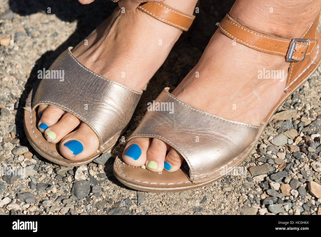 Woman's feet with sandals and painted toenails. - Stock Image