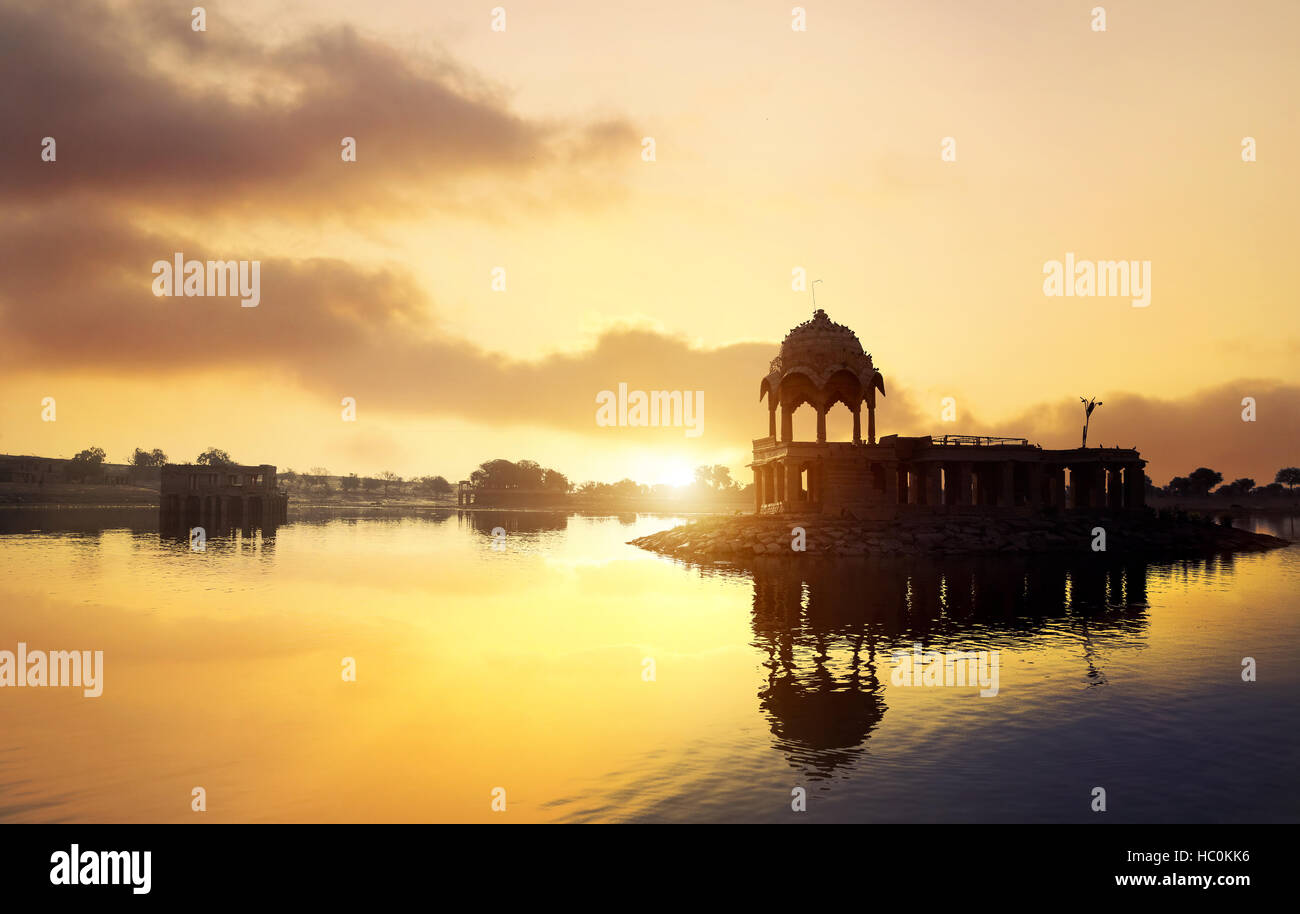 Silhouette of Temple on the Gadi Sagar lake at yellow sunset sky in Jaisalmer, Rajasthan, India - Stock Image