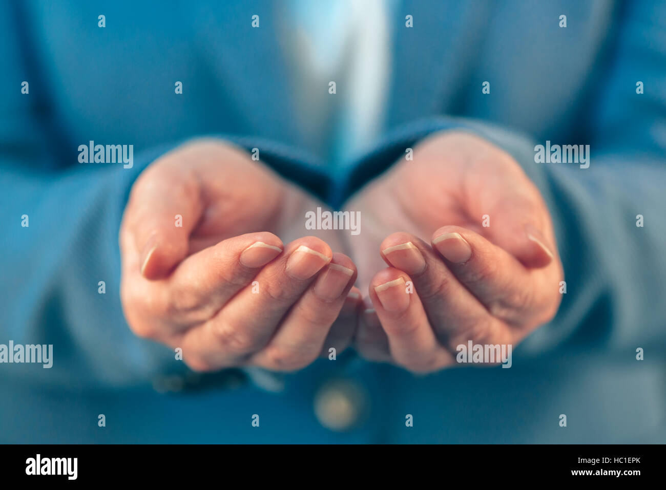 Businesswoman with open palms of her hands asking for something - Stock Image