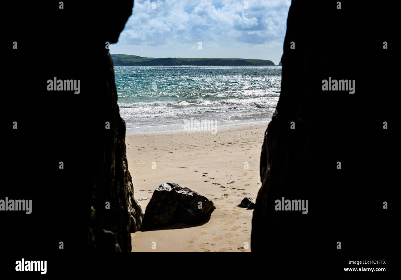 Looking through a cave onto a beach - Stock Image