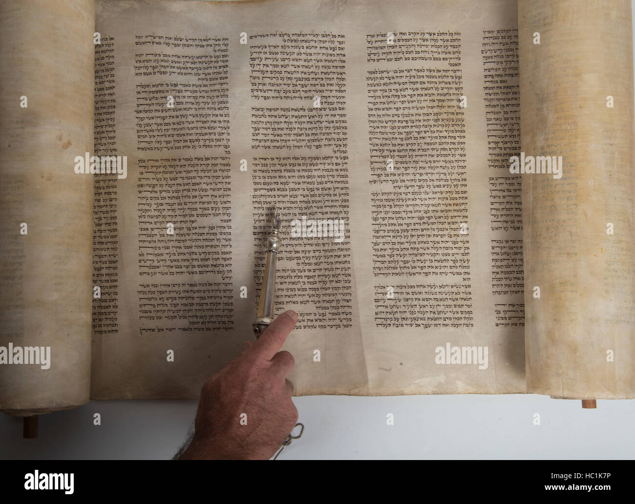 hand of a man reading in an ancient torah scroll - Stock Image