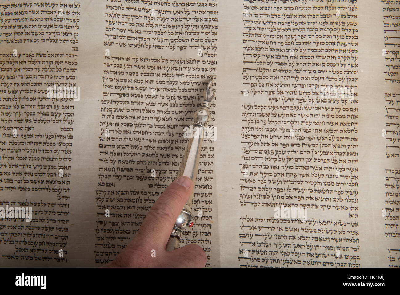 hand of a man reading in an ancient torah script - Stock Image