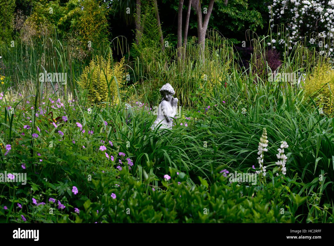 green leaves foliage garden design center centered around statue victorian victorianesque feature gardening RM Floral - Stock Image