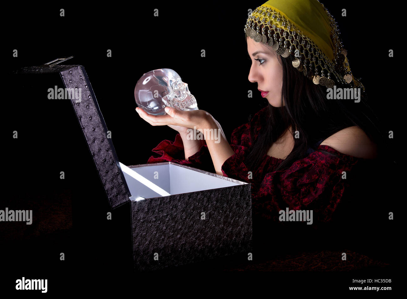 Fortune teller or gypsy opening a glowing mysterious box and discovering treasure.  She is receiving a magical gift - Stock Image