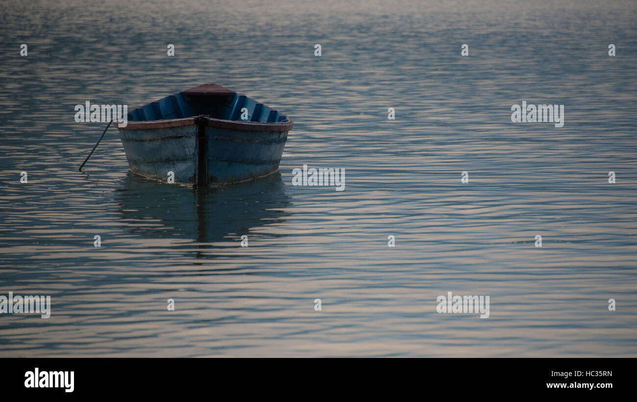 Isolated rowing boat floating in the Lake at dawn in Pokhara - Stock Image