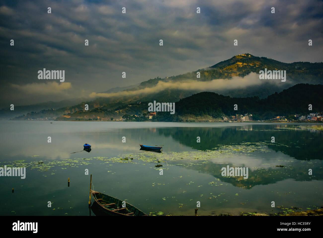 Reflection of Sarangkot hill in Pokhara lake, Nepal - Stock Image