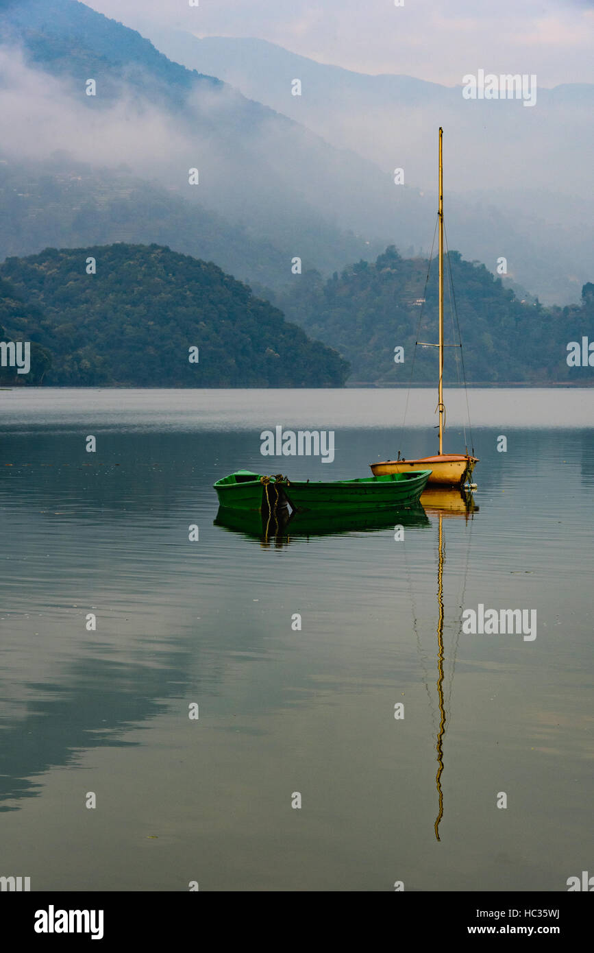 2 boats reflecting in Pokhara lake at dawn - Stock Image