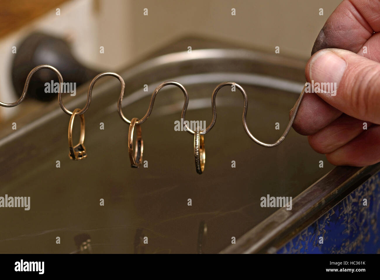 A goldsmith cleans some gold rings in an ultrasonic bath which uses sound waves to dislodge particles from the metal - Stock Image