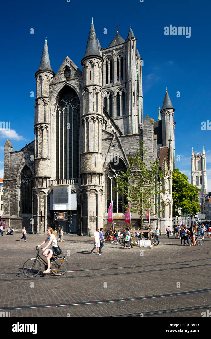 Young people enjoy summer sunshine in streets outside St Nicholas' Church, city centre, Ghent, West Flanders, Belgium, Stock Photo