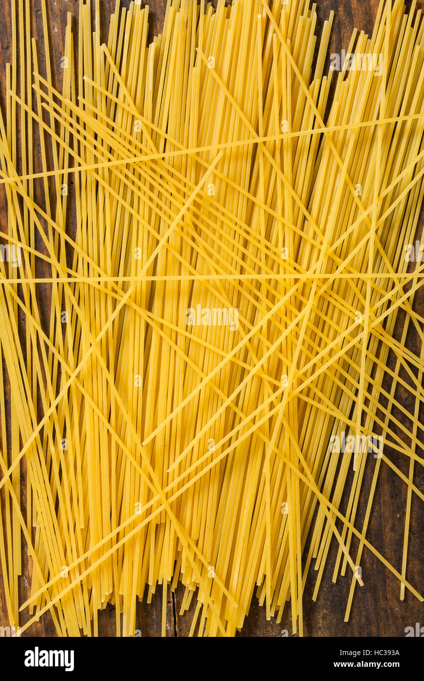 Italian Pasta Yellow Spaghetti As Close Up Top View Still Life Background Image On Rustic Weathered Wooden Board