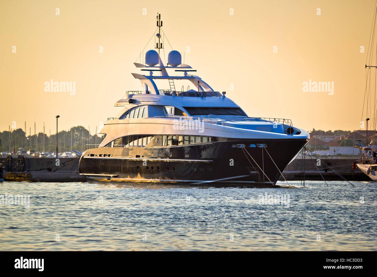 Luxury yacht in harbor on golden sunset - Stock Image