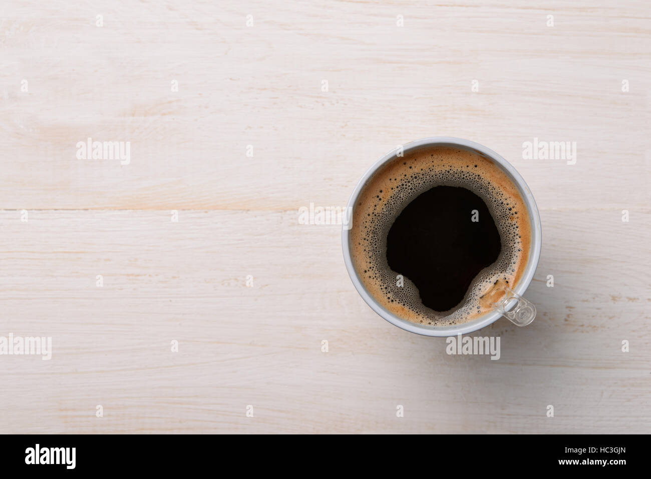 Top view of black coffee in plastic cup on white wooden table - Stock Image