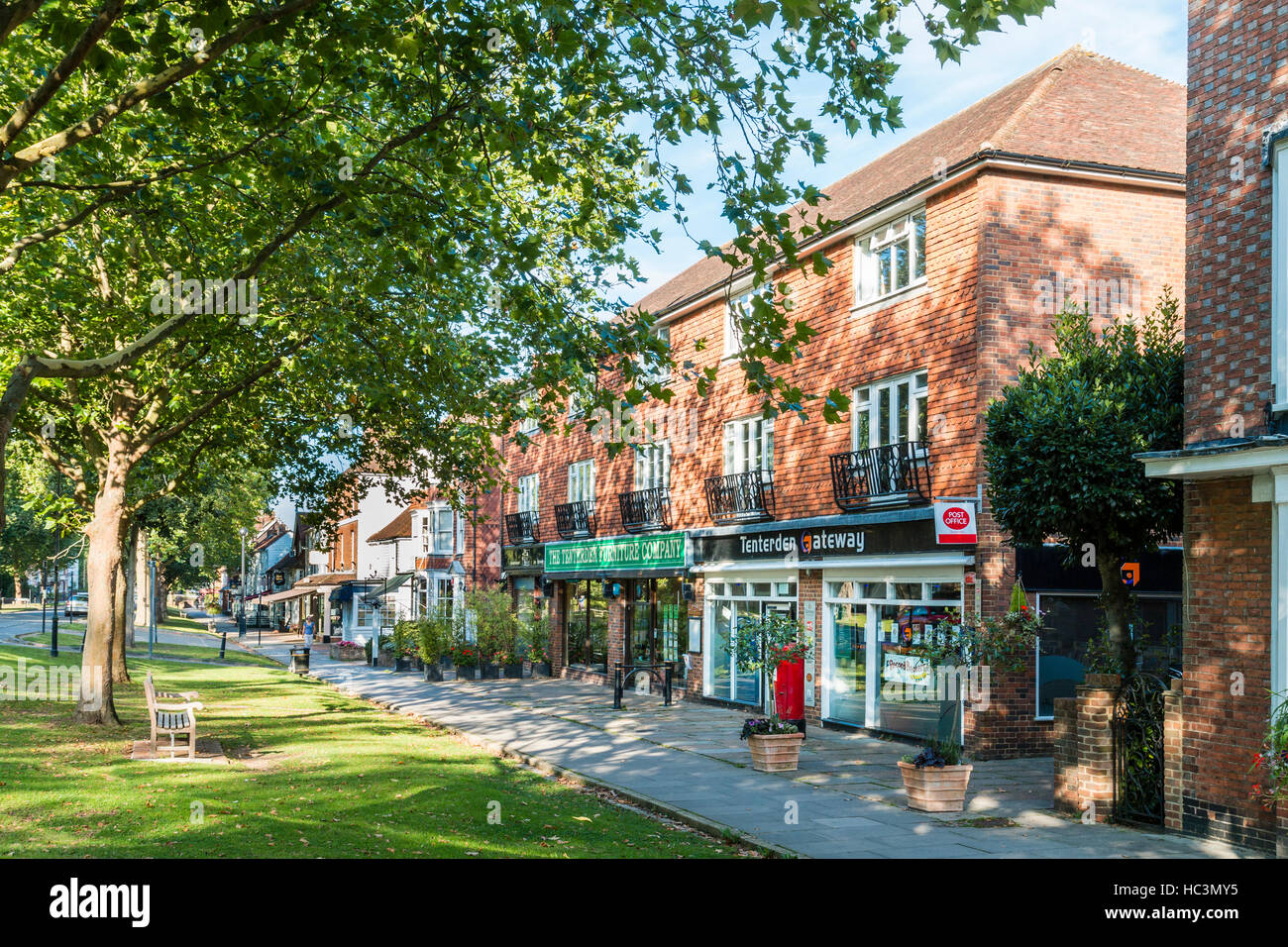 England, Tenterden. The Greens. Tree lined pavement with modern building with shops and post office. Background, - Stock Image