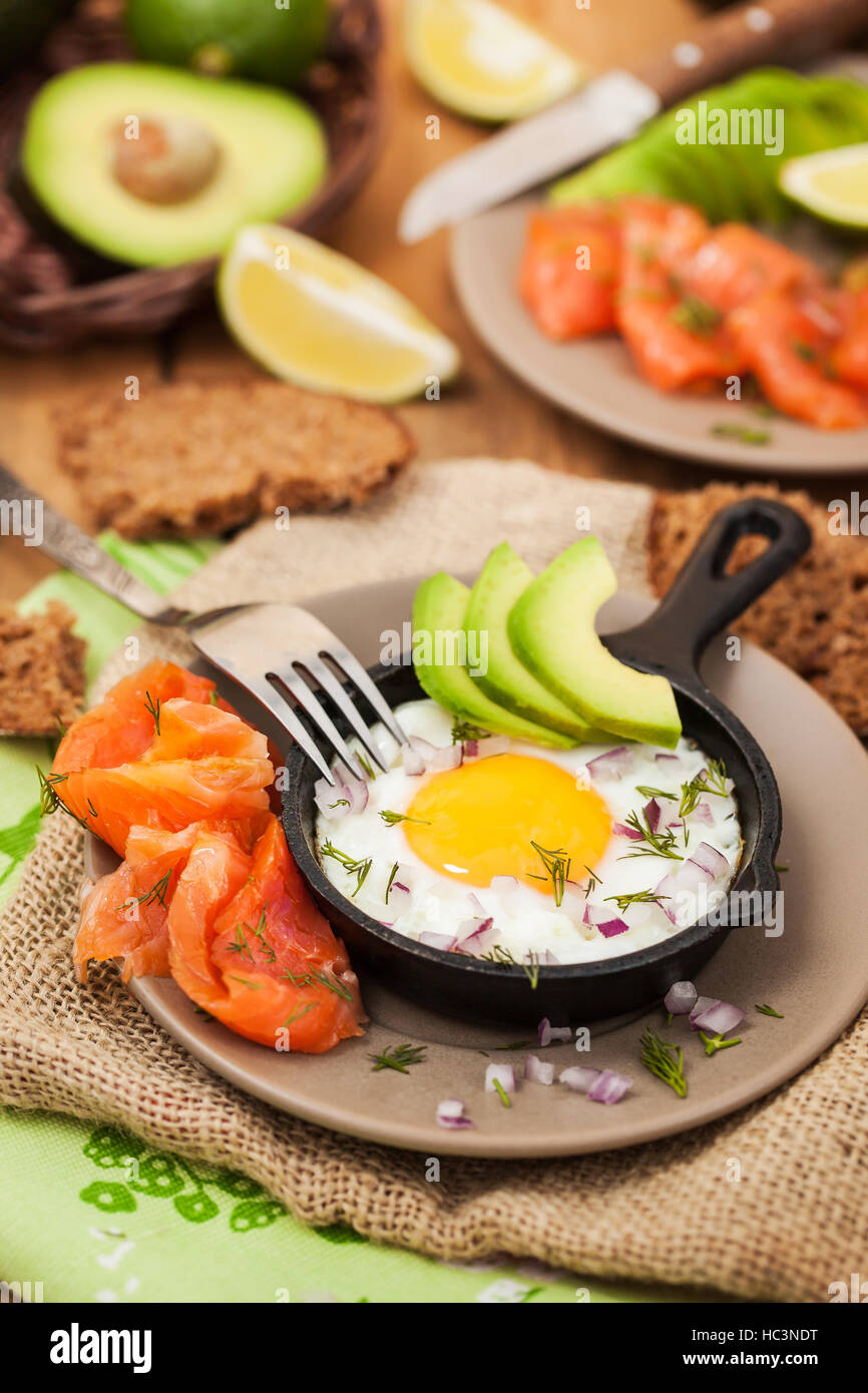 Fried egg, avocado and smoked salmon in frying pan served for breakfast - Stock Image