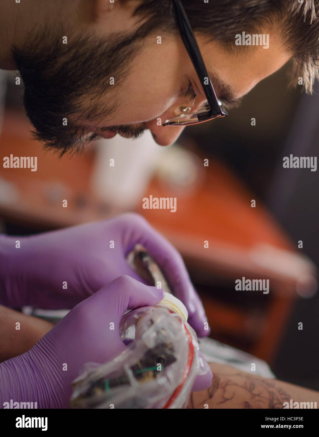 Close up of hand and face tattoo master who holds in his hand Tattoo machine. Soft focus.Focus on face and hand. - Stock Image