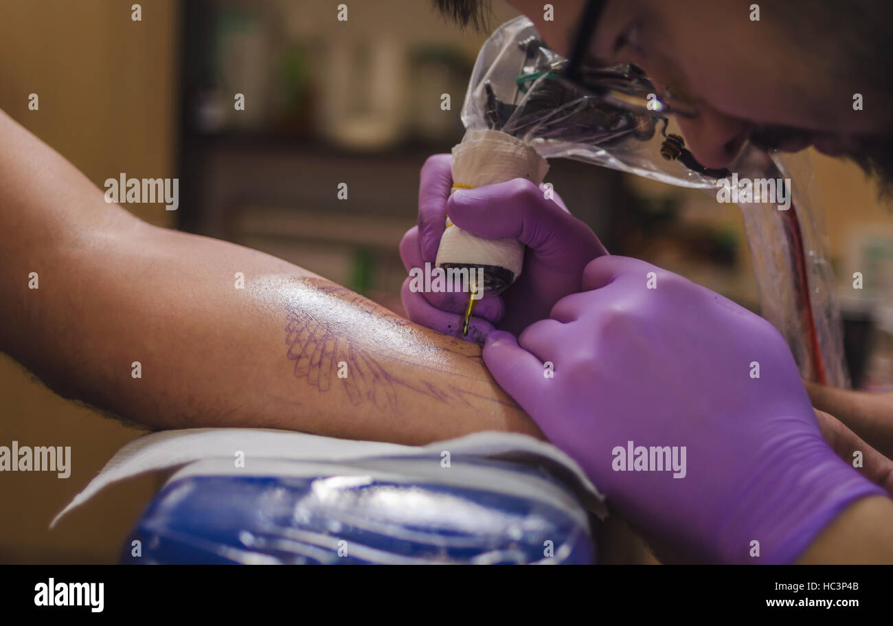 Close-up of a hand and the needle tattoo machine in the process of tattooing. Soft focus. - Stock Image