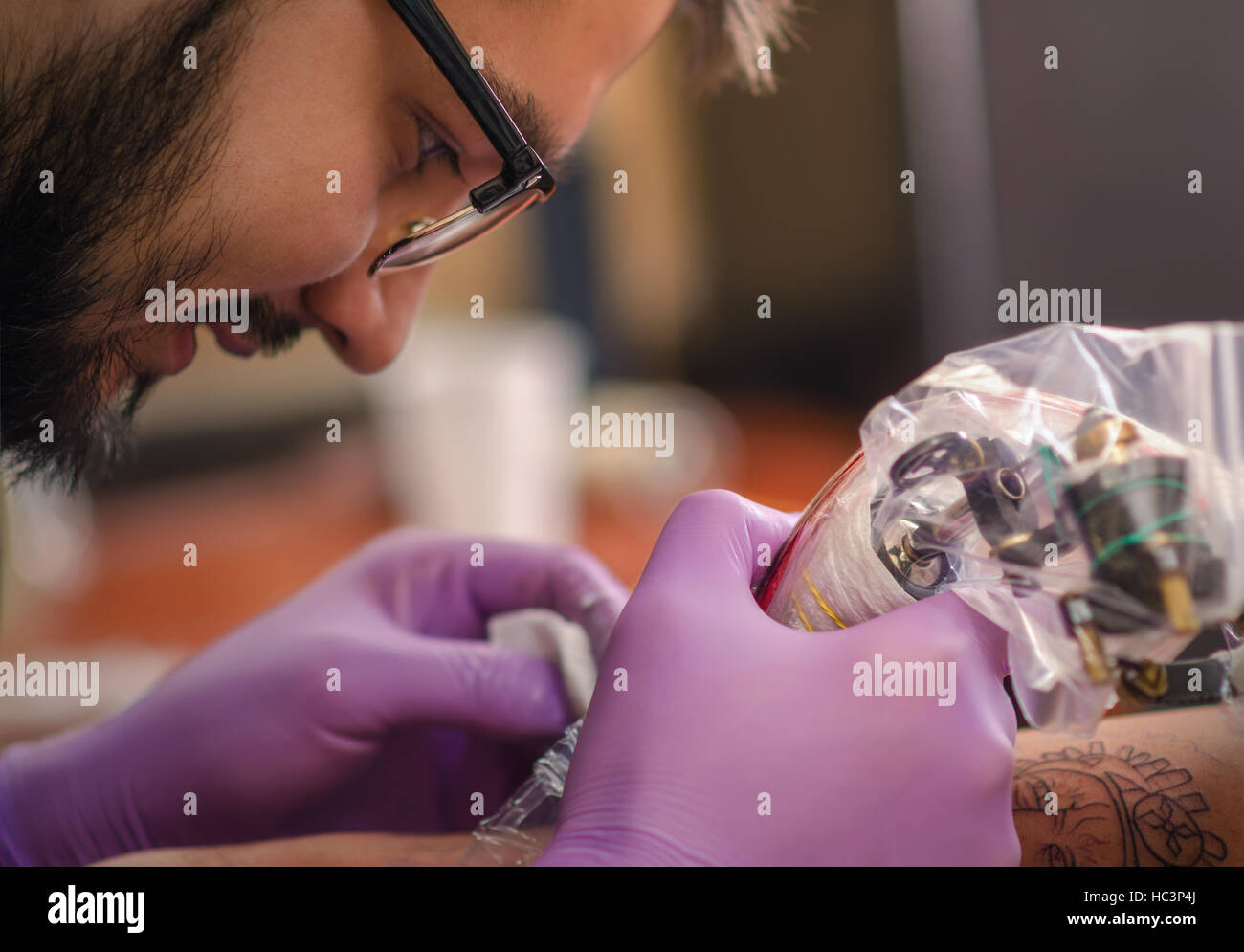 Close up of hand and face tattoo master who holds in his hand Tattoo machine. Soft focus. - Stock Image