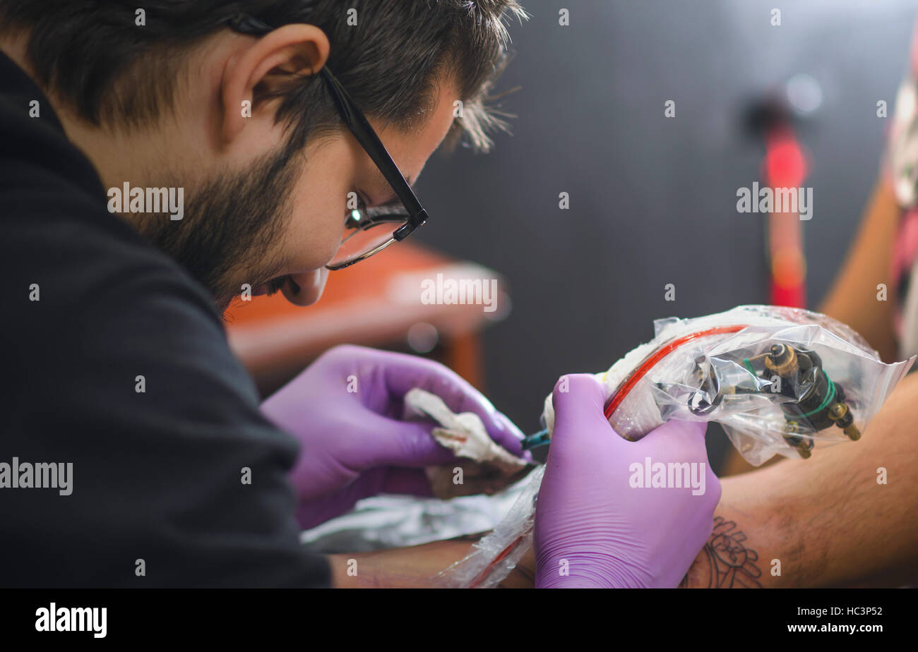 Close up of hand and face tattoo master who holds in his hand Tattoo machine. Soft focus. Focus on face and hand. - Stock Image