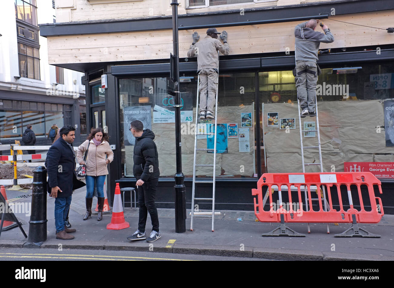 Working on a shop front in London's Soho. - Stock Image