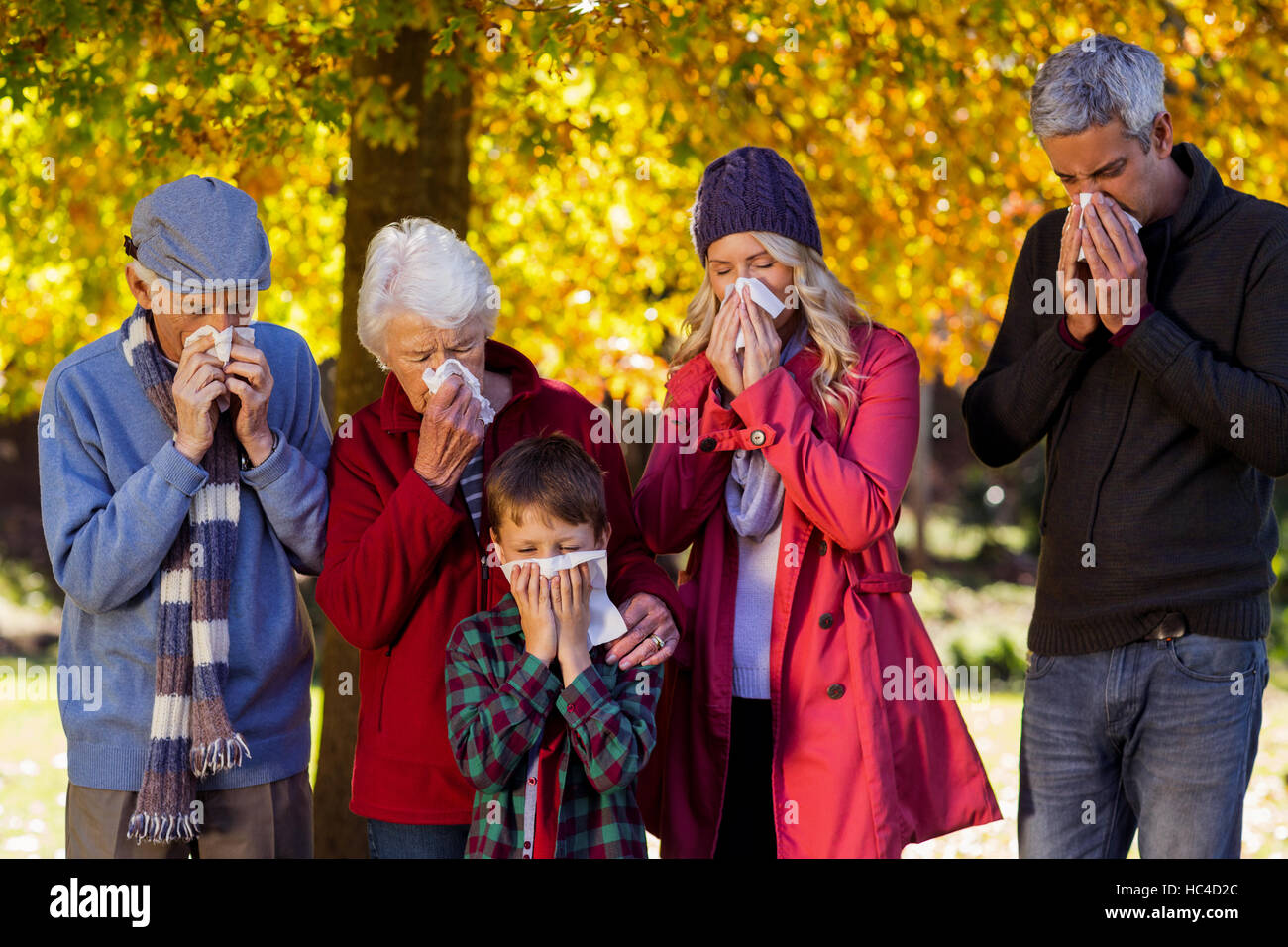 Sick family blowing their noses at park - Stock Image