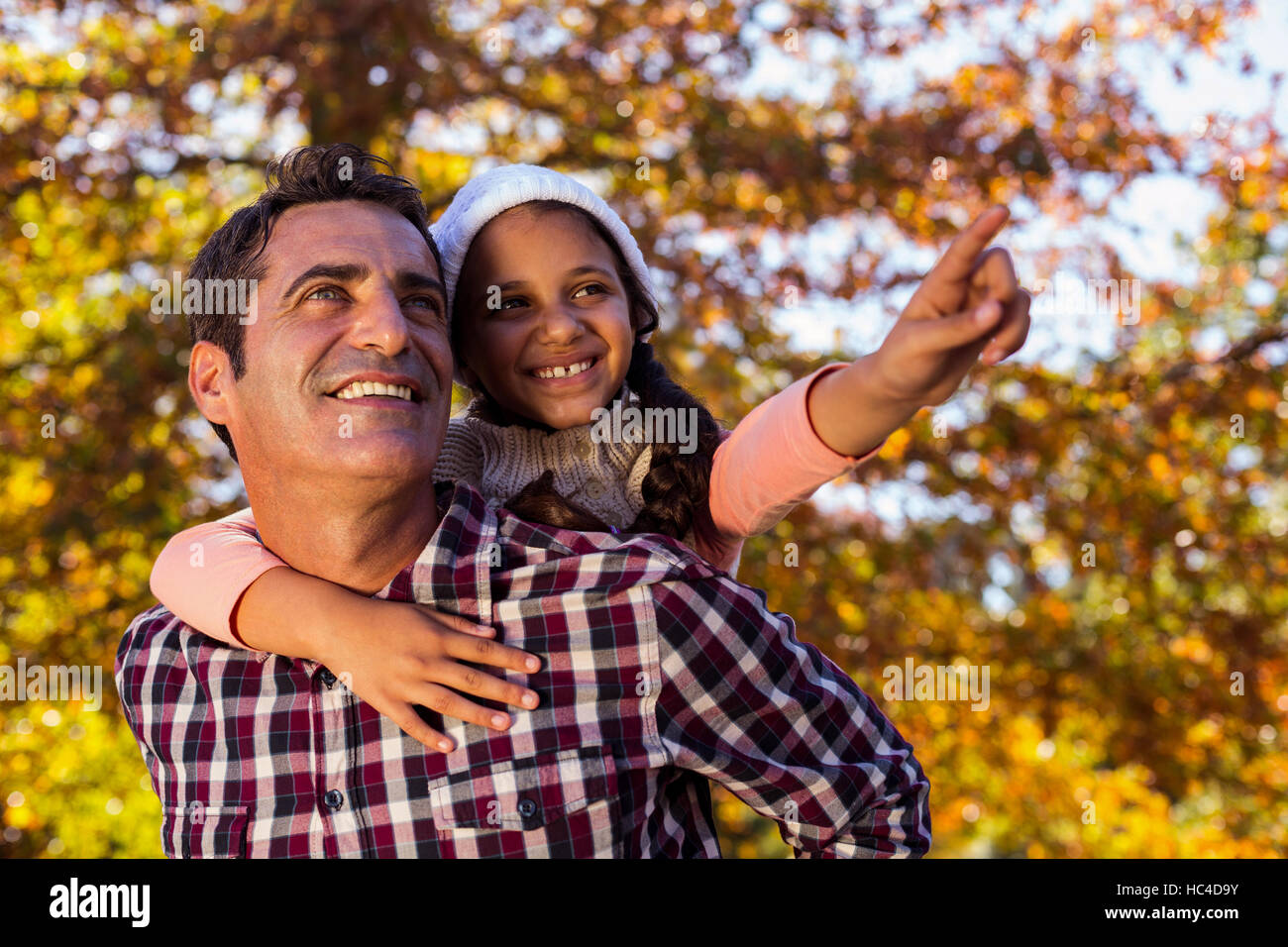 Daughter gesturing while piggybacking with father at park - Stock Image