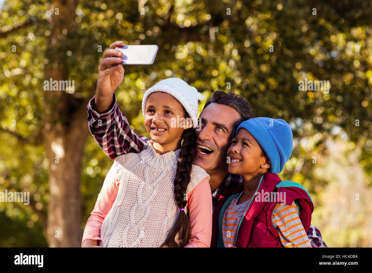 Cheerful father taking selfie with children - Stock Image