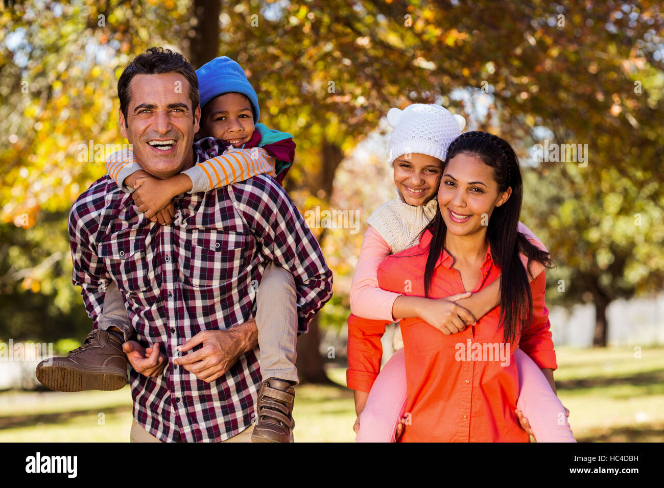 Parents piggybacking children at park - Stock Image