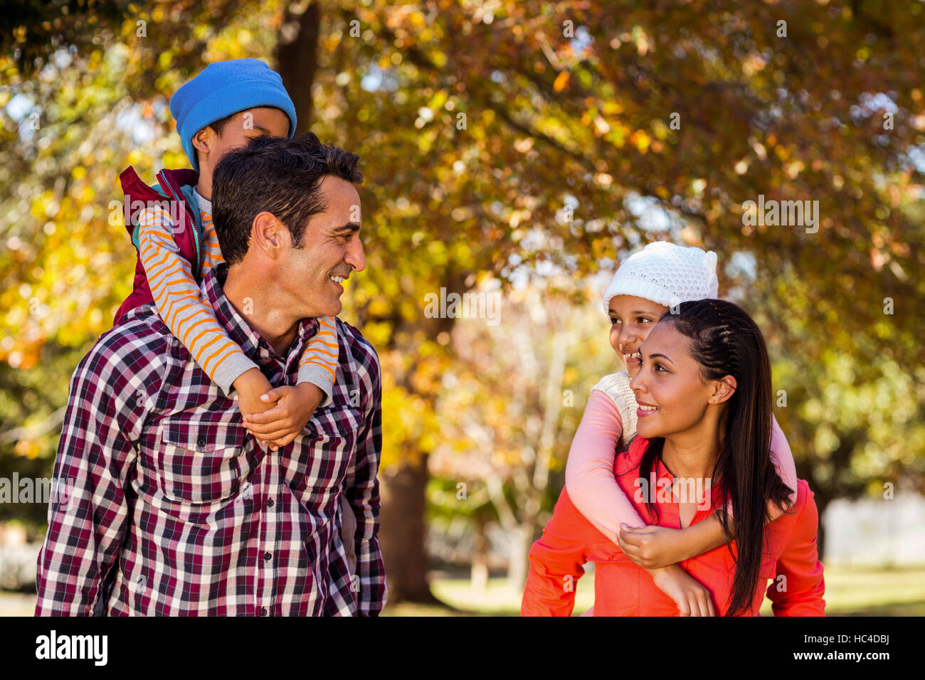 Happy parents piggybacking children at park - Stock Image