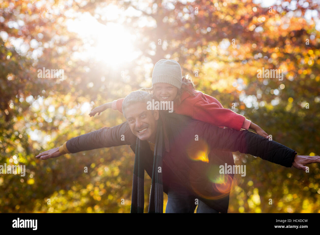 Playful father carrying daughter on back at park - Stock Image