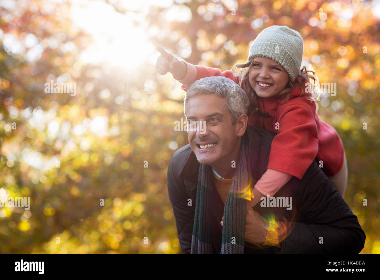 Father piggybacking daughter against autumn trees - Stock Image