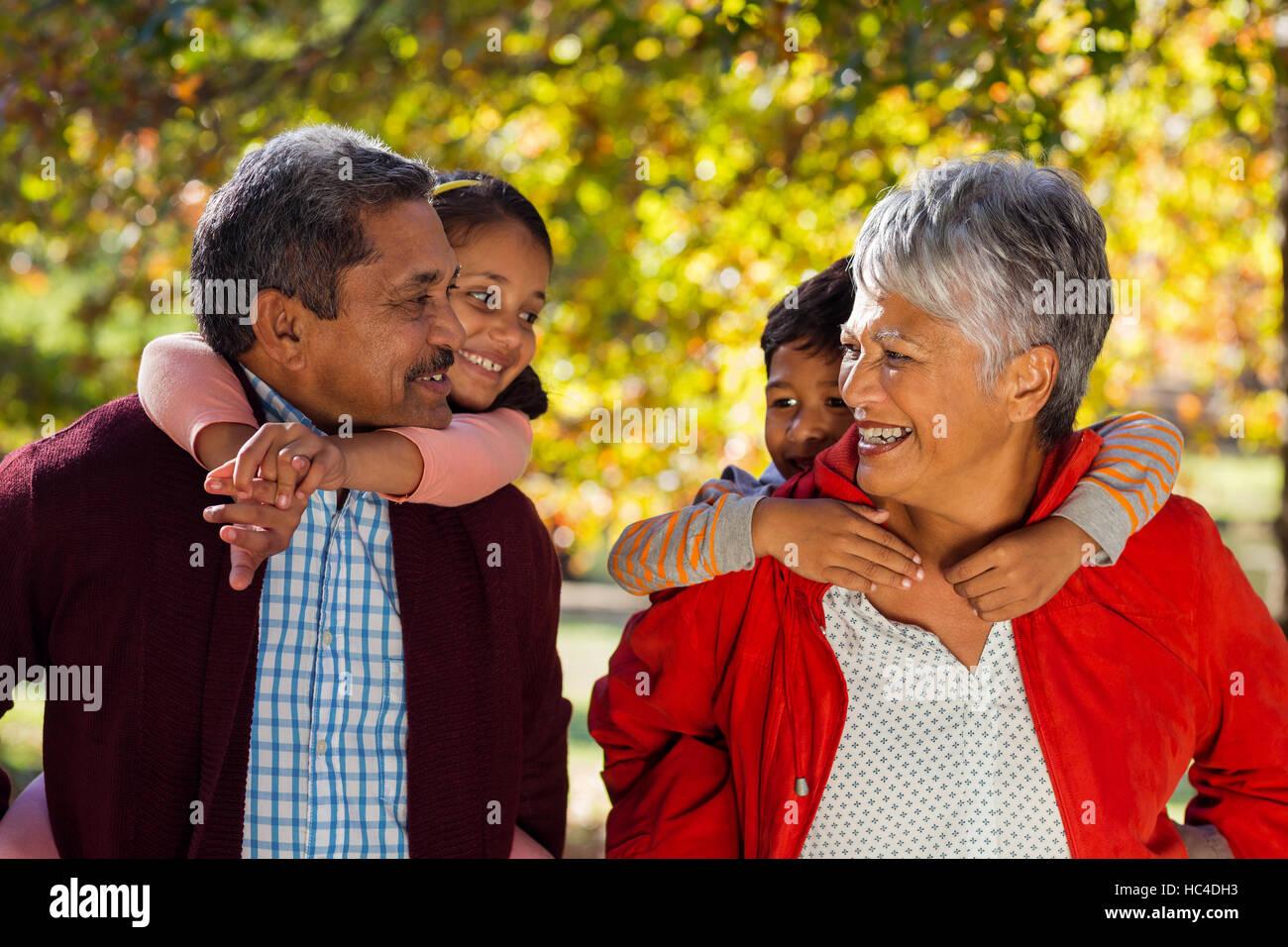 Grandparents piggybacking grandchildren at park Stock Photo