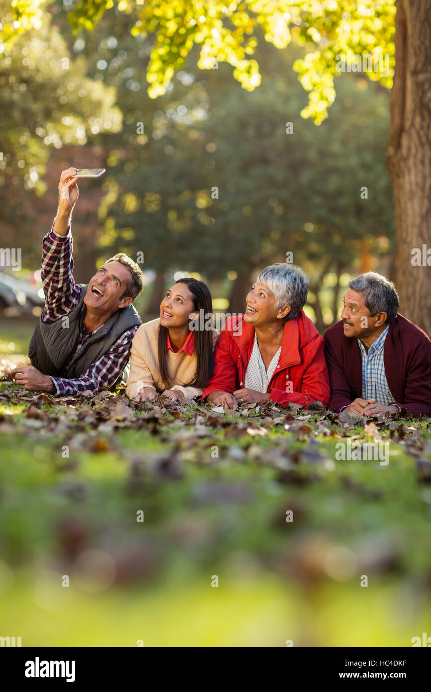 Man with family taking selfie at park - Stock Image