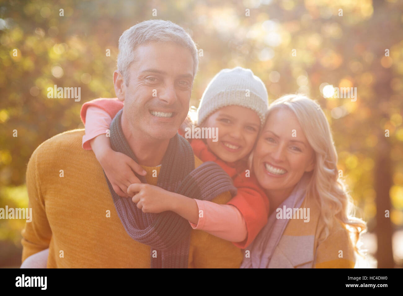 Portrait of happy family against trees - Stock Image