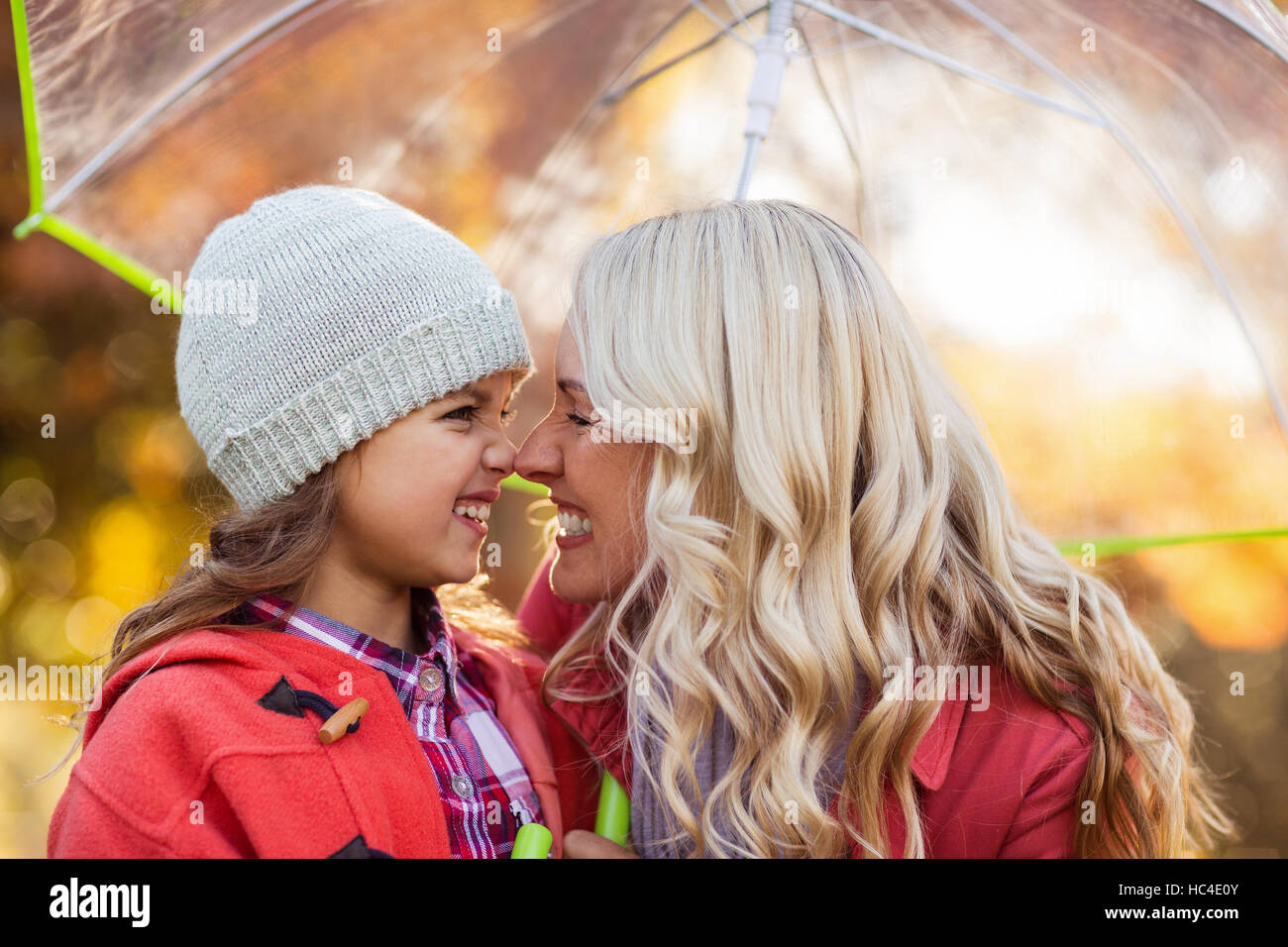 Mother and daughter rubbing noses at park - Stock Image
