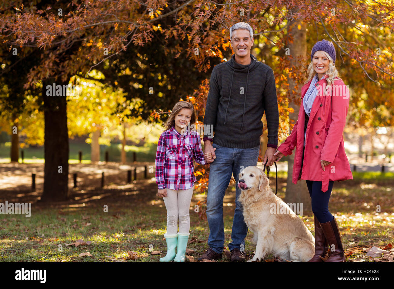 Happy family with dog at park - Stock Image