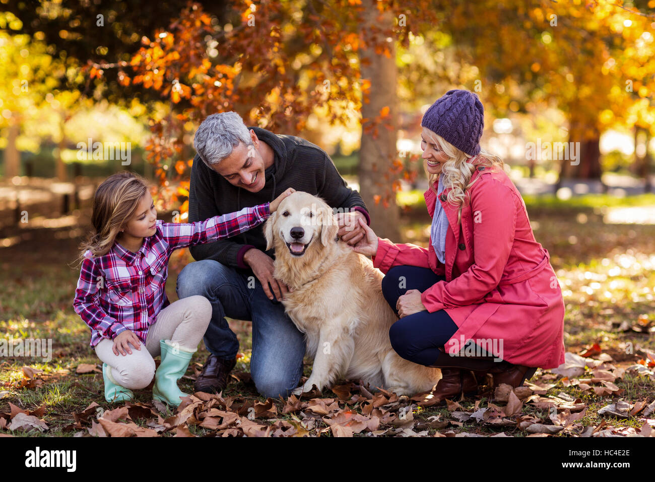 Family stroking dog while crouching at park - Stock Image