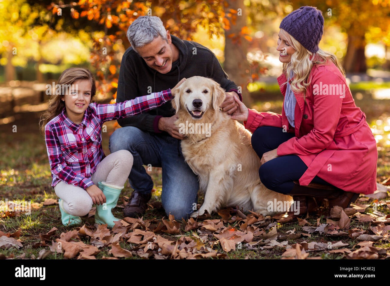 Smiling family with dog at park - Stock Image