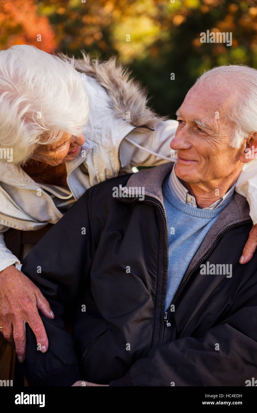 A senior woman tenderly looking at her husband sitting - Stock Image