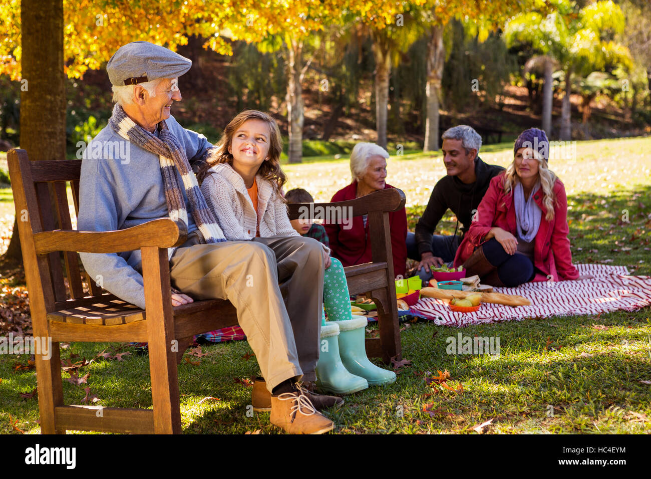 Family picnicking and the grandfather laughing with his grand daughter on a bench - Stock Image