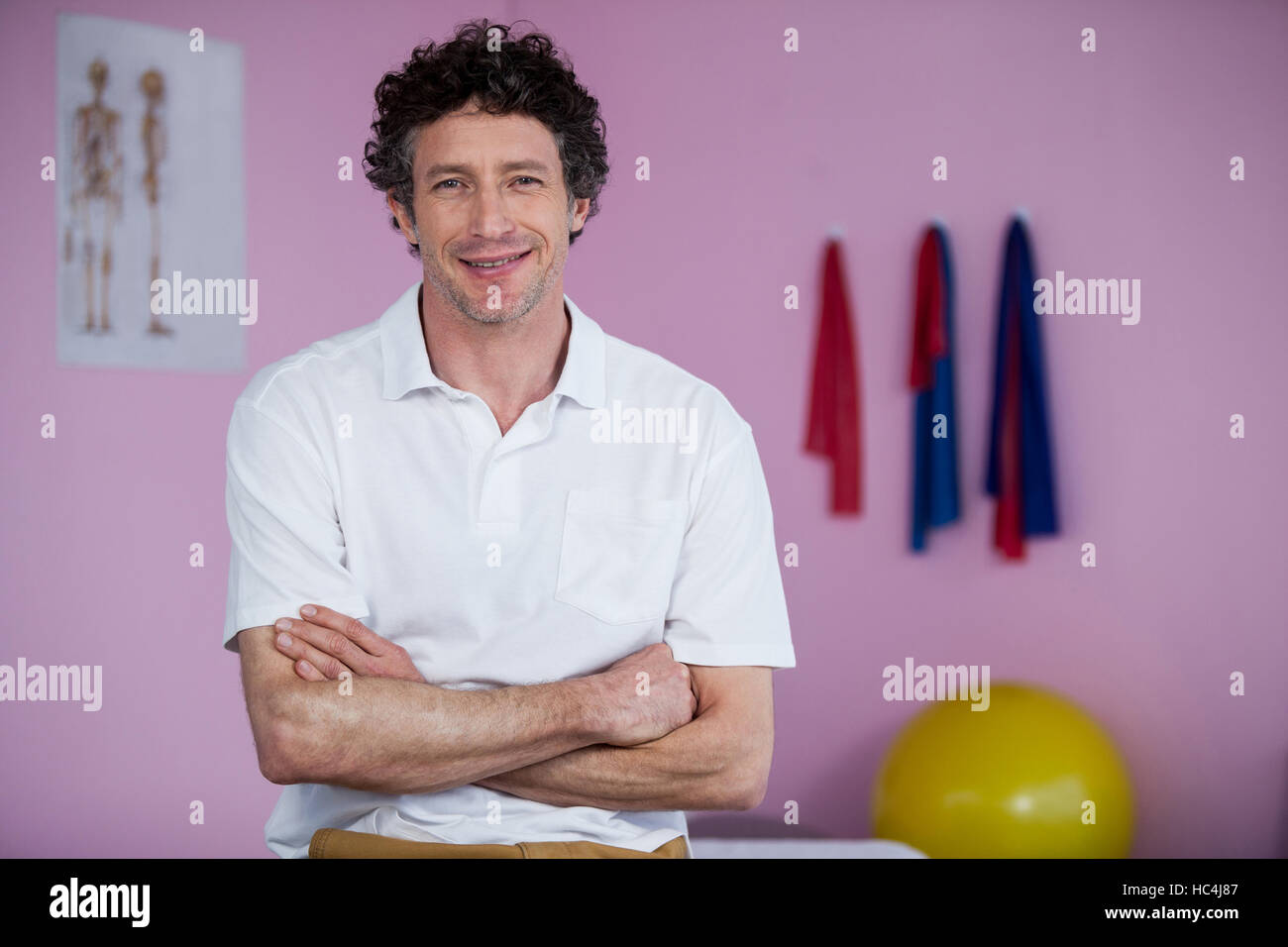 Portrait of physiotherapist standing with arms crossed - Stock Image