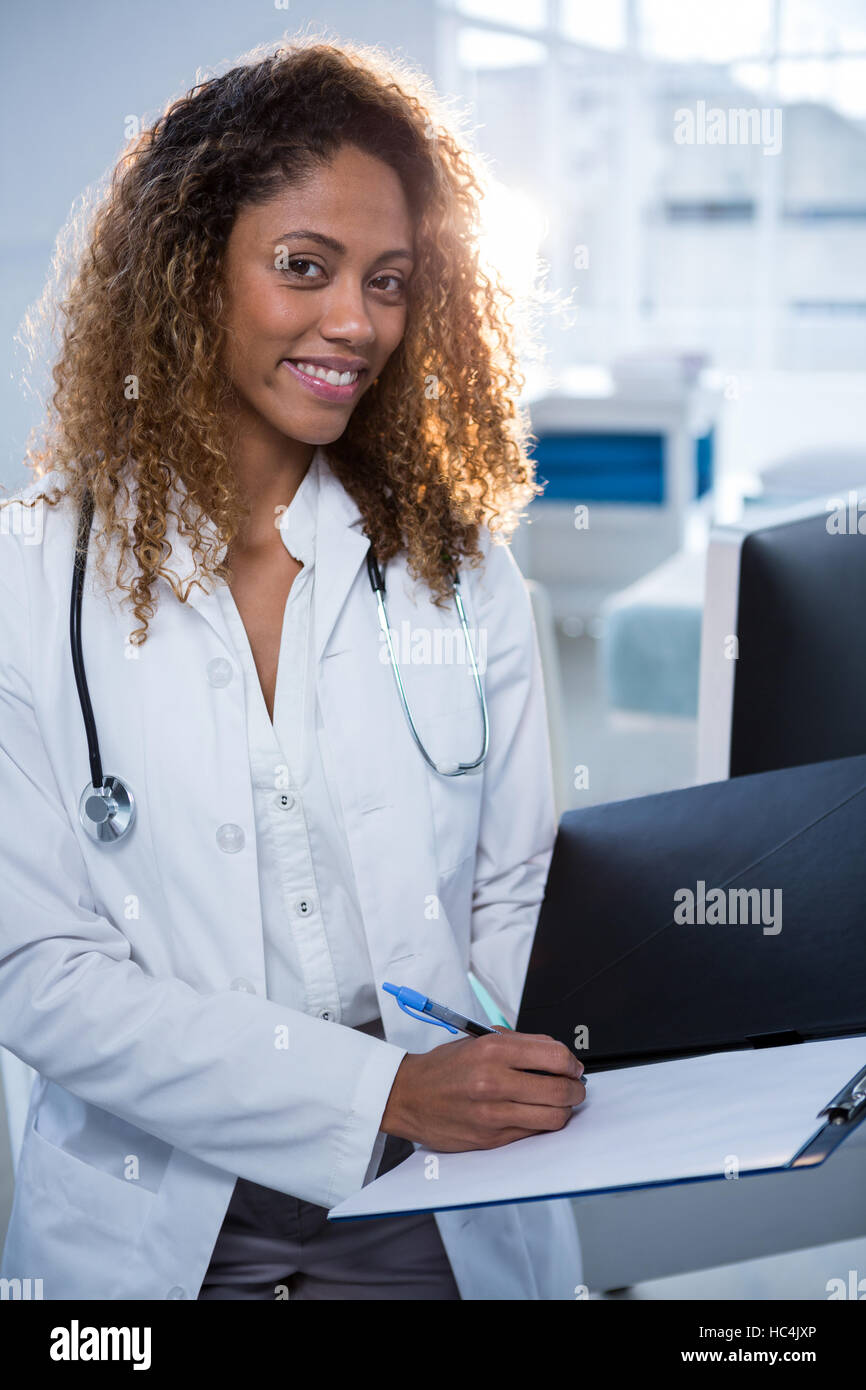 Physiotherapist writing on clipboard - Stock Image