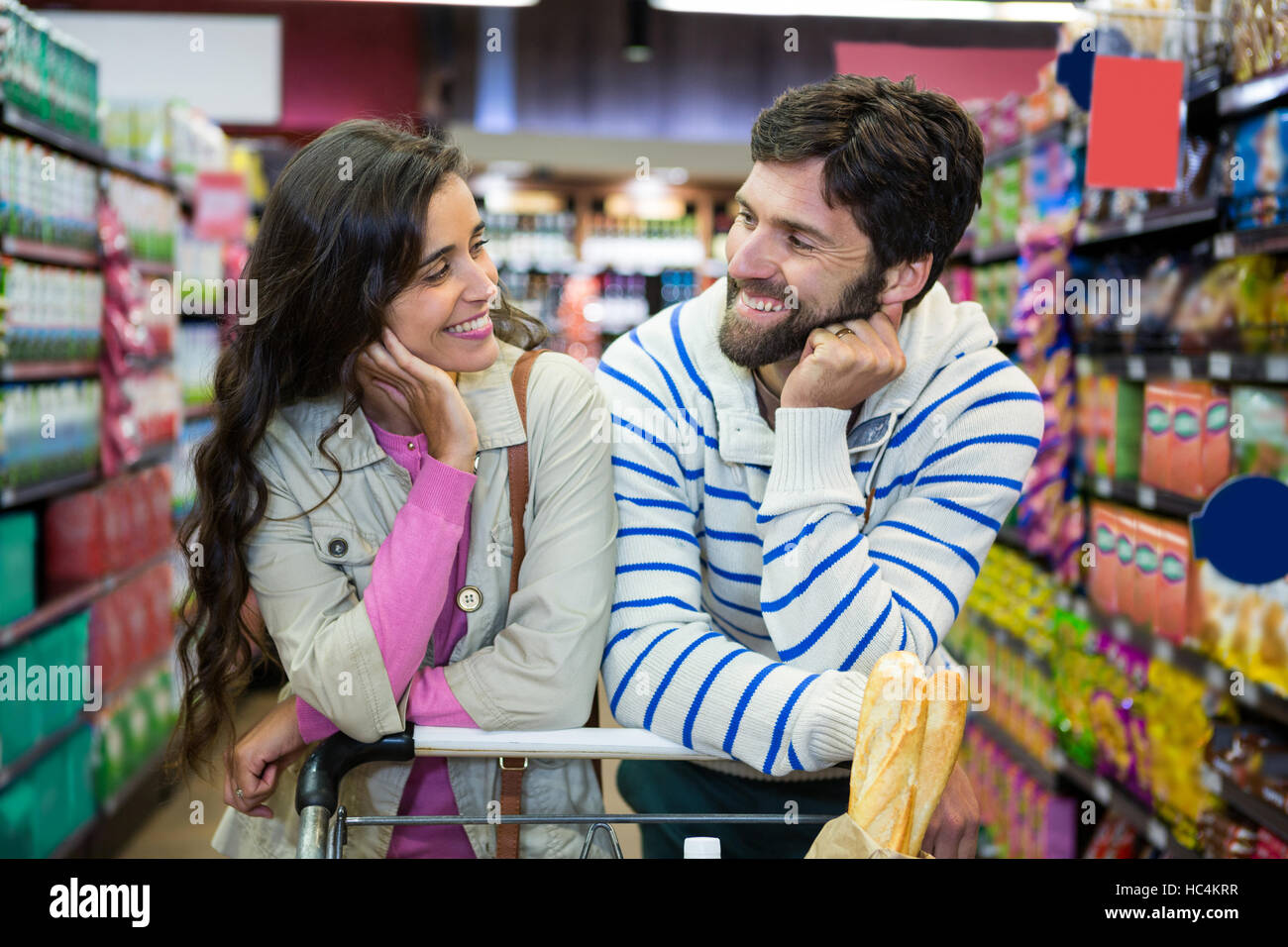 Couple leaning on trolley at supermarket - Stock Image