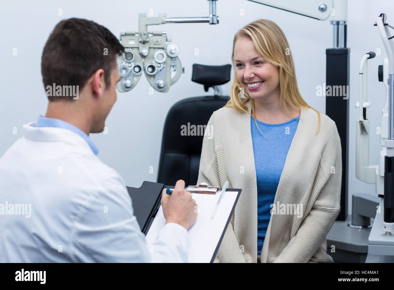 Optometrist consulting female patient - Stock Image