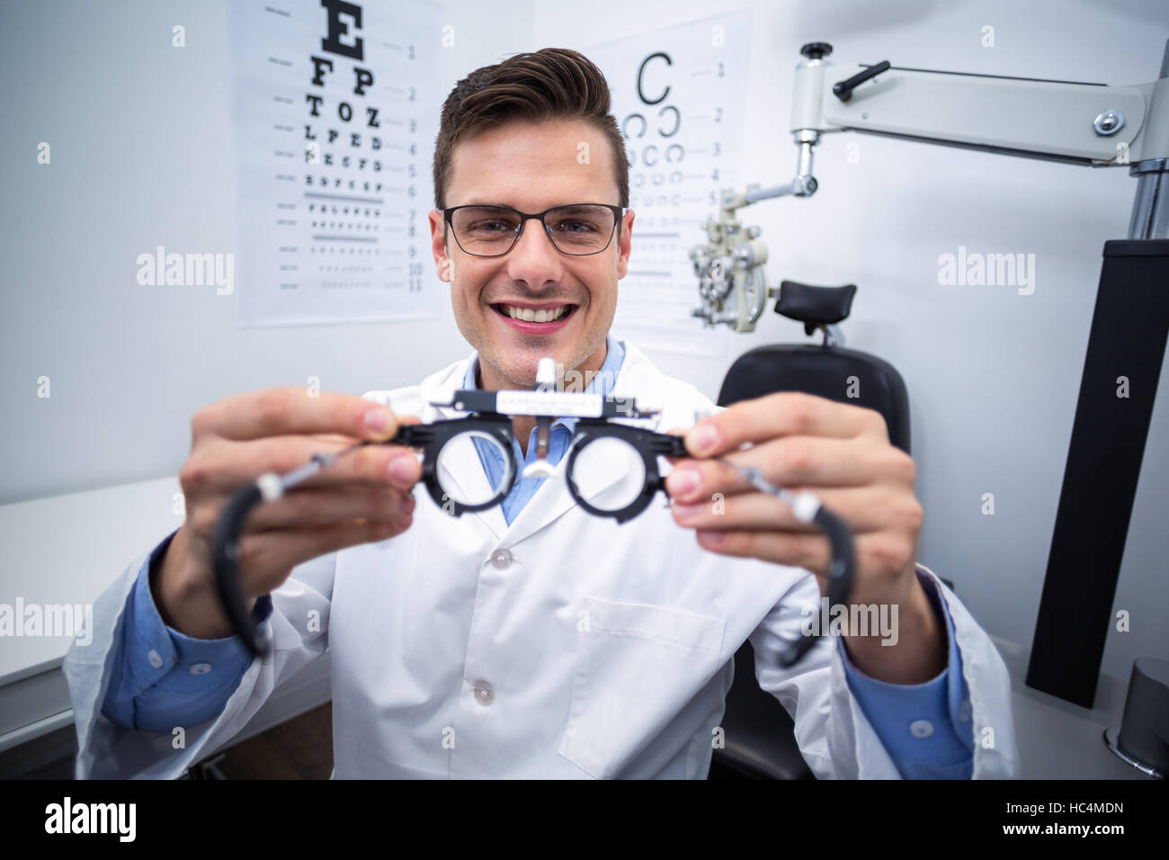 Smiling optometrist holding messbrille - Stock Image