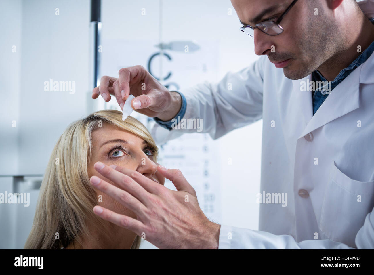 Optometrist putting drops into patients eyes - Stock Image