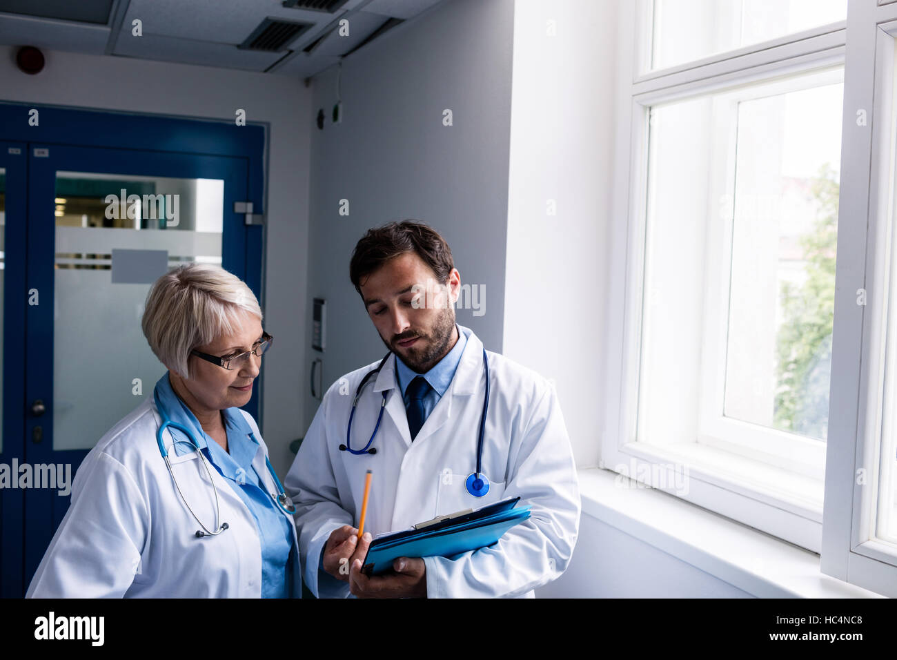 Doctors discussing over clipboard - Stock Image