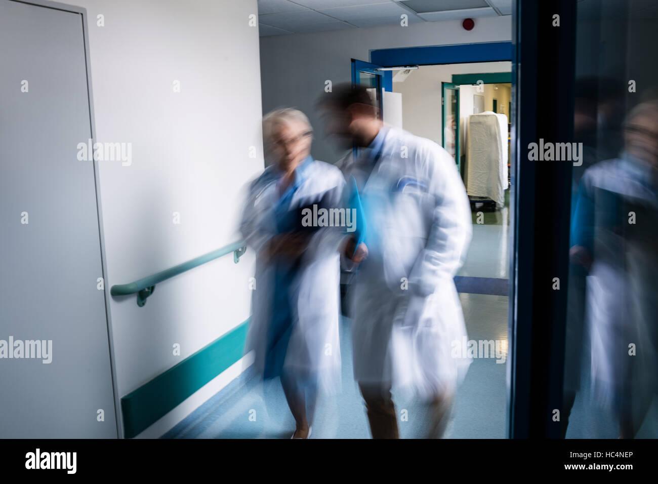 Blur view of doctors walking in corridor - Stock Image
